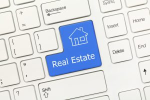 Close-up view on white conceptual keyboard - Real Estate (blue key)